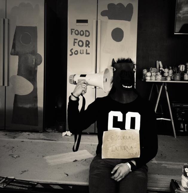 Collègue de Thierry Noir plaisantant avec un masque et posant devant les frigos en train d'être peints dans le cadre du projet Grunding. Il tient dans ses mains une affichette fabriquée pour le Journal International - Crédit Chloé Marchal