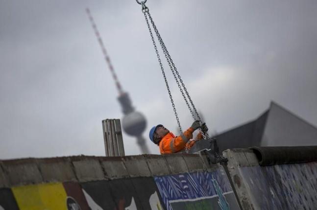 Un ouvrier attache un morceau du mur à une grue devant les manifestants, 1er mars 2013 - @Thomas Peter pour Reuters