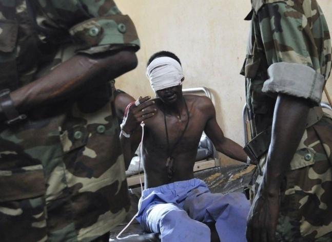 Des rebelles du Séléka parlent, le 29 mars 2013, avec l'un des leurs soigné dans un hôpital de Bangui   Photo : Agence France-Presse Sia Kambou