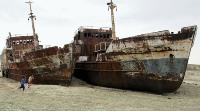 Children run past ruined ships abandoned in sand that once formed the bed of the Aral Sea. Lake Balkhash in Kazakhstan faces the danger of becoming another Aral Sea because of upstream diversion by China. Crédits photo — Reuters