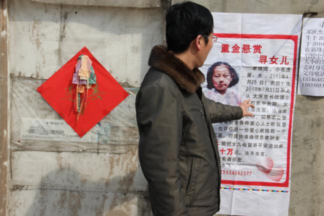 Un homme devant le poster signalant le rapt d'un enfant
