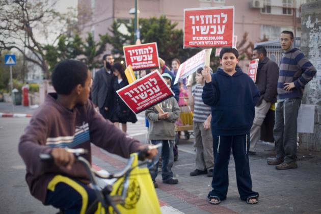 Habitantes de Tel Aviva agitan pancartas « Volven a casa » dirigidas a un chico negro. Crédito Foto -- Oren Ziv / ActiveStills