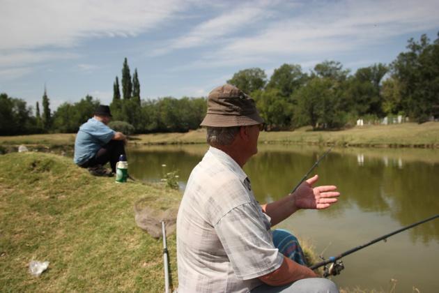 Anatoliy et son ami de l'association des pêcheurs discutent de la baisse du niveau d'eau dans les réserves. Crédit : Novastan.org