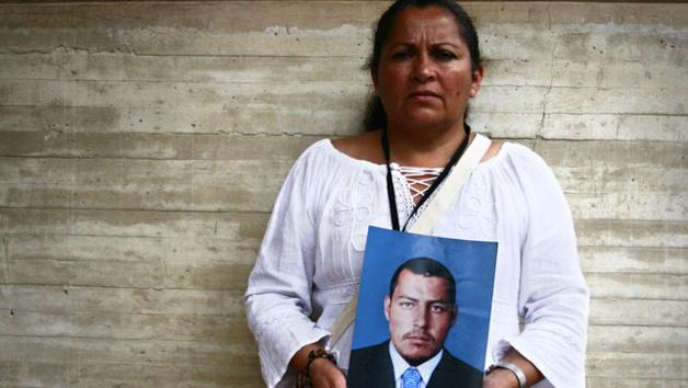 Une mère montrant le portrait de son fils assassiné par l'armée. Crédit Emma Gascó