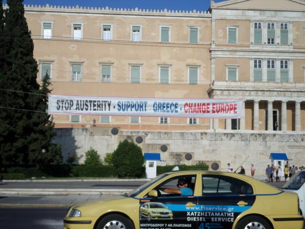 Una pancarta izada frente al Parlamento griego – Crédito: Amélia Viguier