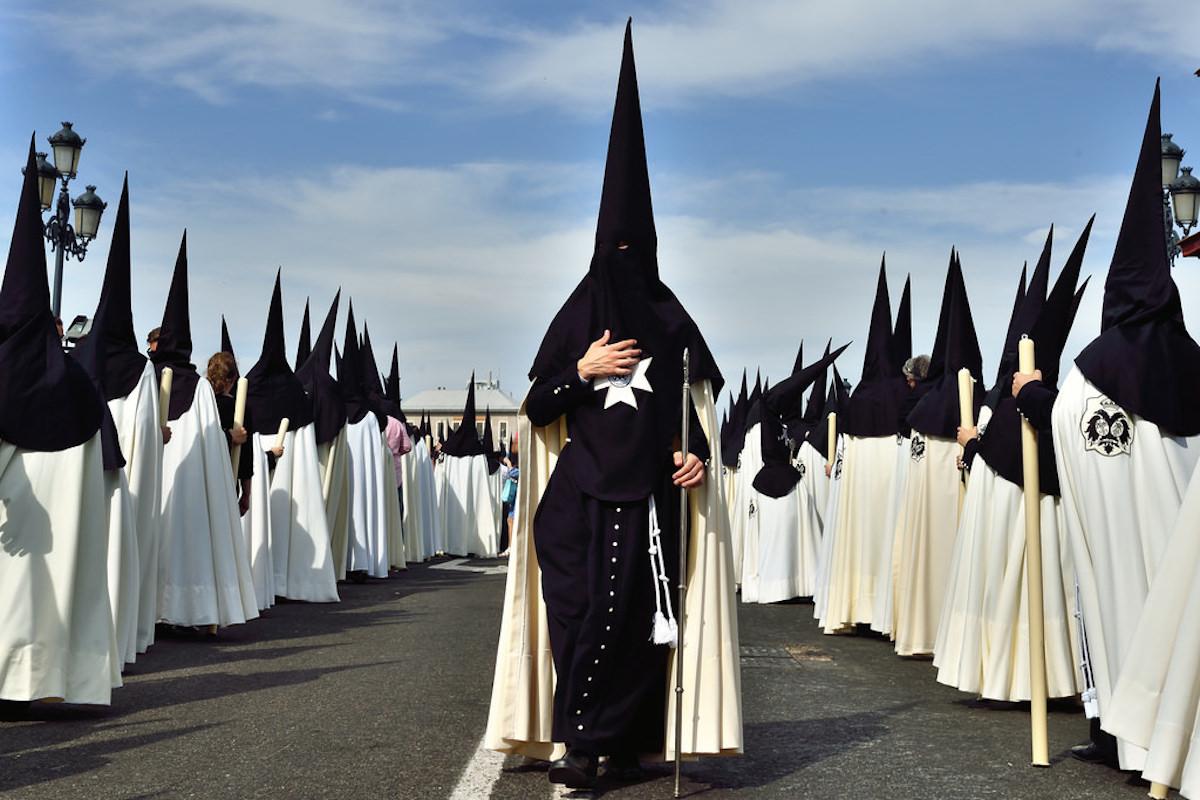 Procession de pénitents appelés « nazarenos » lors de la Semaine Sainte à Séville. Crédit : Flickr / César Catalan